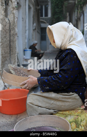 Women sitting outside of their houses and sieving the mastic in Pyrgi villafe on Chios island Greece - Stock Photo