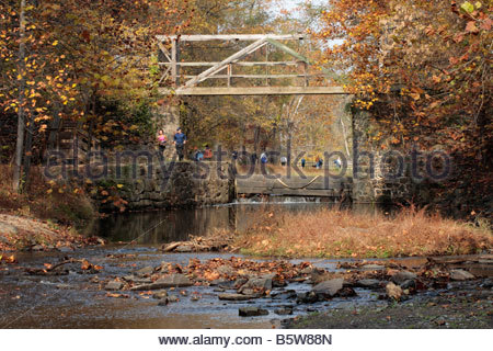 Hikers and runners pass the stop gate and footbrige near Lock 16 on the C&O Canal in Maryland. - Stock Photo
