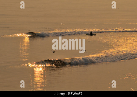 Catch the Golden Wave - surfers waiting for and catching waves in the waters off of Topanga State Beach, California - Stock Photo