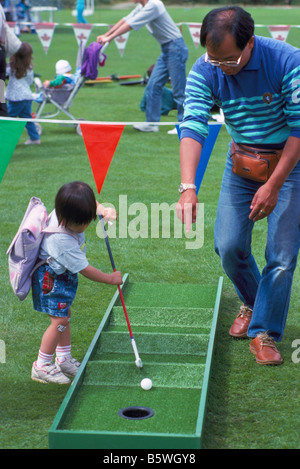 Young Asian Girl playing Miniature Golf and assisted by her Father - Stock Photo