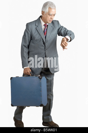 Businessman carrying a suitcase and checking the time - Stock Photo