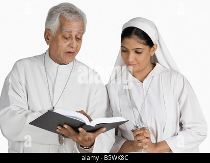 Priest and a nun looking at the Bible - Stock Photo