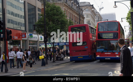 Two Red London buses pass in Oxford Street London GB UK - Stock Photo