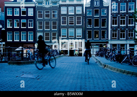 cyclists crossing a bridge at dusk in amsterdam - Stock Photo