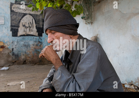 An Egyptian man in the City of the Dead or Cairo Necropolis where some people live and work amongst the dead in - Stock Photo