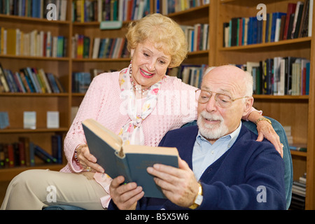 Senior couple enjoying a good book together in the library - Stock Photo