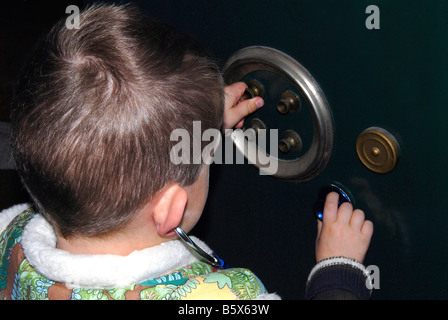 Young boy, 6 years, trying to open the door of grandfather ' safety box - Stock Photo