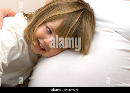 Young girl listens to her mothers pregnant tummy. - Stock Photo