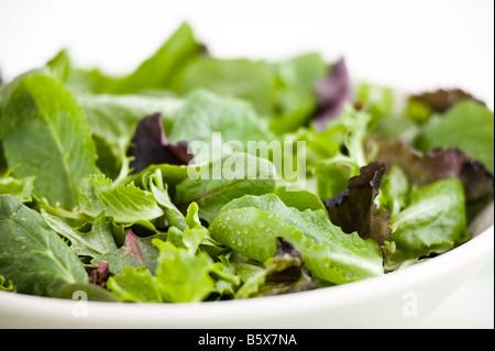 lettuce in a white bowl on a white linen napkin - Stock Photo