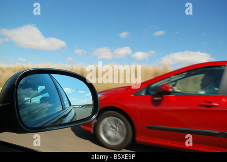 Rear view mirror and car driving along the road. - Stock Photo