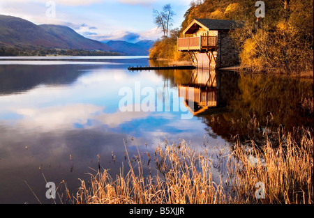 Early morning light falls on a boathouse near Pooley Bridge on the shores of Ullswater in the Lake District - Stock Photo
