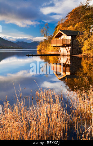 Early morning light falls on the boathouse near Pooley Bridge on the shores of Ullswater in the Lake District England - Stock Photo