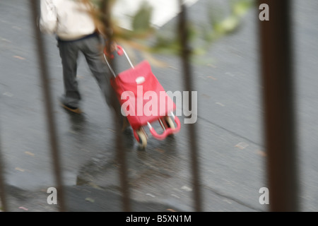 man with shopping trolley walking in rain in town - Stock Photo