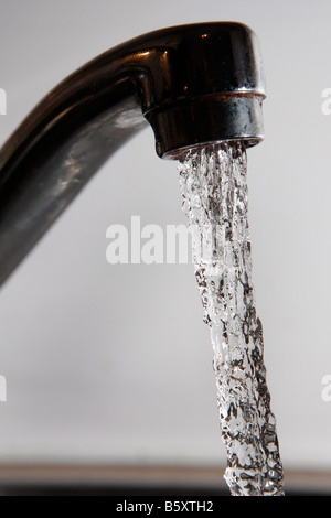 Water gushing from a domestic tap fawcet - Stock Photo