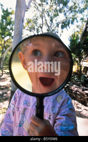 Young girl with magnifying ^glass - Stock Photo