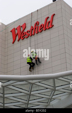 Westfield shopping centre in Shepherds Bush West London abseilers roped access technicians working on iconic Westfield - Stock Photo