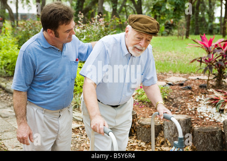 Senior man struggling to us a walker His adult son is helping him - Stock Photo