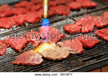 steaks on bbq grill flamed with torch - Stock Photo