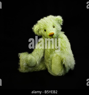 Hand made pale green teddy bear with orange sewn nose sitting on a black background. Made by Rhiw Valley Bears. - Stock Photo