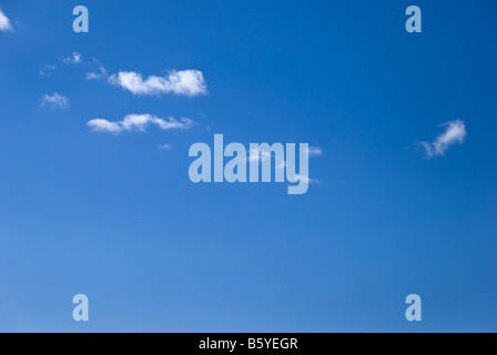 A line of fluffy or cotton wool like clouds float against a perfect clear blue sky - Stock Photo