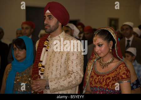 Sikh groom and bride in gurdwara or temple on wedding day - Stock Photo