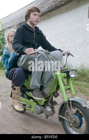 Boy driving a moped. A girl is sitting behind him. Non of them wearing a helmet. - Stock Photo