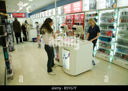 A teenage girl buying articles in Boots the Chemist, Lion Yard, Cambridge, UK - Stock Photo