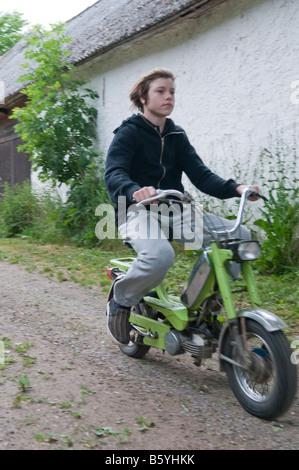 Boy, not wearing a helmet, driving a moped. - Stock Photo