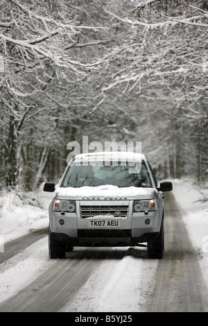 Land Rover Freelander 2 four wheel drive vehicle driving along a snow covered rural road in winter, in Scotland, - Stock Photo