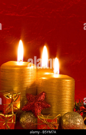 Three burning candles in a Christmas setting with seasonal decorations - Stock Photo