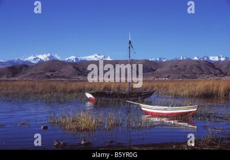 Fishing boats at Puerto Perez, Cordillera Real behind, Lake Titicaca, Bolivia - Stock Photo