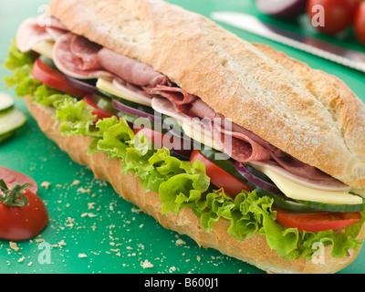Deli Sub Sandwich on a Chopping Board - Stock Photo