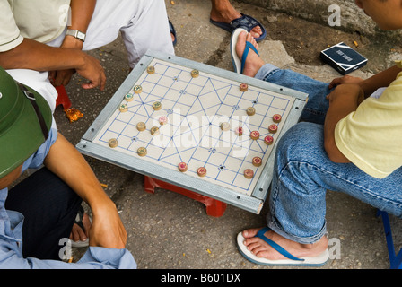 Men playing Xiangqi - Chinese Chess or Vietnamese Chess on the streets of Ho Chi Minh City, Vietnam - Stock Photo
