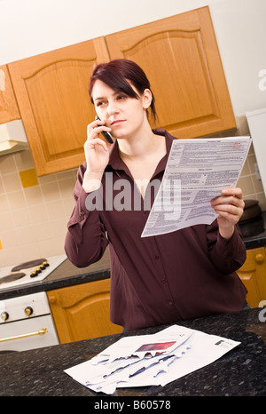 Young woman at home querying a large bill using her mobile phone listening and looking sceptical MR PR - Stock Photo
