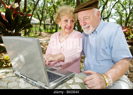 Senior couple on the computer The wife is pointing something out to the husband - Stock Photo