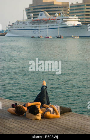 Couple resting at Rambla de Mar in Barcelona Spain Europe - Stock Photo