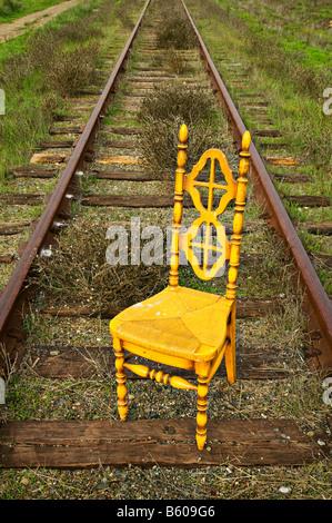 Yellow chair on railroad tracks - Stock Photo