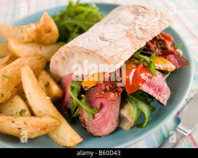 Steak and Roasted Pepper Ciabatta Sandwich with Spiced Potato Wedges - Stock Photo