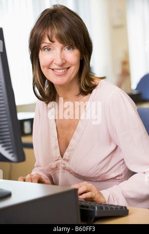 Woman sitting at a computer terminal typing (high key)