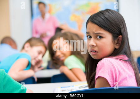 Student in class being bullied by students in background (selective focus) - Stock Photo