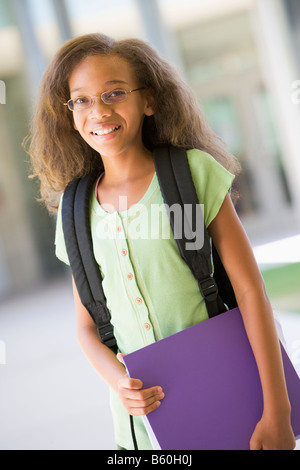 Student standing outside school holding binder and smiling (selective focus) - Stock Photo