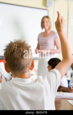 Student volunteering in class with teacher at board (selective focus) - Stock Photo