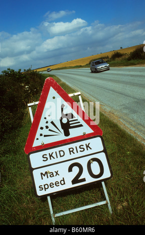 cars passing warning sign of slippery road surface on newly resurfaced road near Leeds Yorkshire UK - Stock Photo