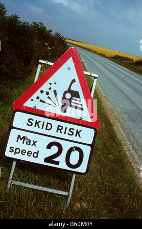 warning roadsign of slippery road surface on newly resurfaced road near Leeds Yorkshire UK - Stock Photo