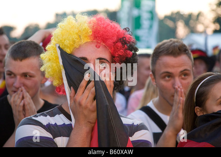 Fan wearing a wig with the colours of the German flag watching the final game of the football EM on the Berlin fan mile, Berlin