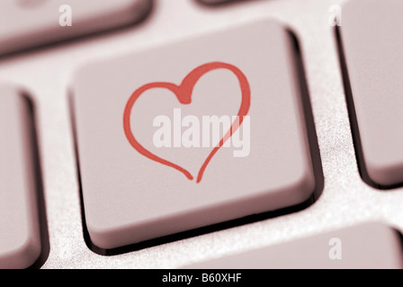 Heart shape on a computer keyboard, symbolic image for internet dating - Stock Photo