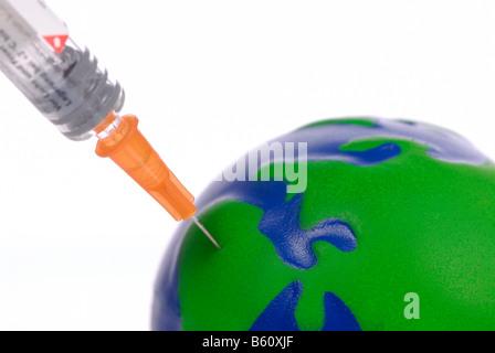 Inoculation syringe injected into a miniature globe, symbolic image for travel inoculation, climate change or environmental - Stock Photo