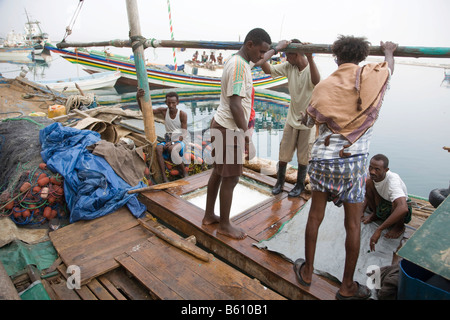 Workmen loading ice onto a boat in the fishing harbour, Massawa, Red Sea, Eritrea, Horn of Africa, East Africa - Stock Photo