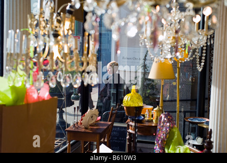 A woman walks past an antiques shop window in New Haven Connecticut USA - Stock Photo