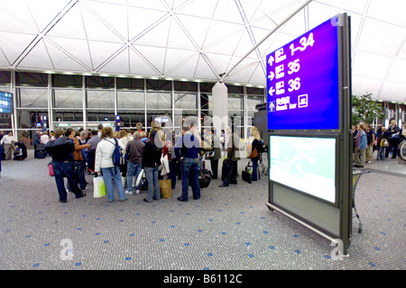 Wide angle view of passengers queing at a departure gate in Chek Lap Kok airport, Hong Kong. - Stock Photo